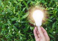 Main de personne tenant l'ampoule pour l'idée ou le succès ou l'e solaire Photos libres de droits