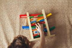 Main de petit garçon jouant avec l'abaque Photo haute de Clouse de l'enfant en bas âge mignon bouclé jouant avec le jouet en bois Images libres de droits