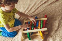 Main de petit garçon jouant avec l'abaque Photo haute de Clouse de l'enfant en bas âge mignon bouclé jouant avec le jouet en bois Image libre de droits