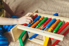 Main de petit garçon jouant avec l'abaque Photo haute de Clouse de l'enfant en bas âge mignon bouclé jouant avec le jouet en bois Photo libre de droits