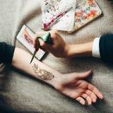 Main de photo étant décorée du tatouage de henné Photographie stock