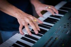 Main de pianiste avec l'anneau sur le piano Images libres de droits
