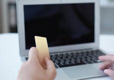 Main de plan rapproché des détails de dactylographie de carte de crédit de fille sur l'ordinateur portable au processus complet d image libre de droits