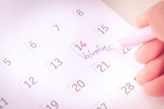 Main de plan rapproché marquant le 14 février Images stock