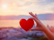 Main de plan rapproché tenant le coeur rouge pendant le fond de coucher du soleil Photo libre de droits