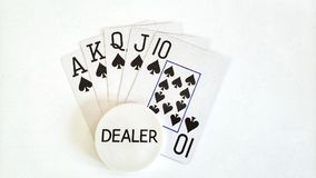 Main de poker de quinte royale et bouton de revendeur photographie stock