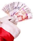 Main de Santa Claus avec le rouble russe d'argent. Photo stock