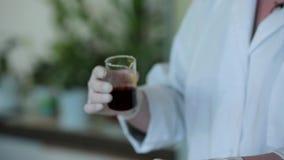 Main de scientifique versant une solution chimique d'un tube à essai en verre de laboratoire dans un cylindre scientifique avec l clips vidéos