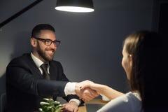 Main de secousse masculine heureuse de demandeur de travail féminin pendant l'entrevue photo libre de droits