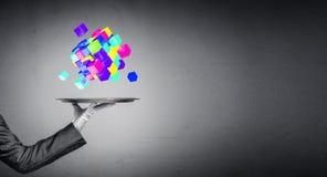 Main de serveur présentant des cubes sur le plateau Photos libres de droits