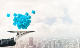 Main de serveur présentant des cubes sur le plateau Image libre de droits