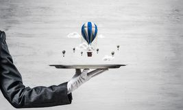 Main de serveuse présentant des ballons sur le plateau Photos libres de droits