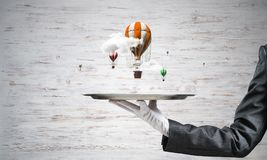 Main de serveuse présentant des ballons sur le plateau Photographie stock