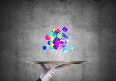 Main de serveuse présentant des cubes sur le plateau Photo stock