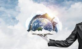 Main de serveuse présentant le globe de la terre sur le plateau Image libre de droits
