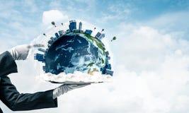 Main de serveuse présentant le globe de la terre sur le plateau Photographie stock