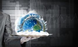 Main de serveuse présentant le globe de la terre sur le plateau Photo stock