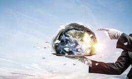 Main de serveuse présentant le globe de la terre sur le plateau Photos stock