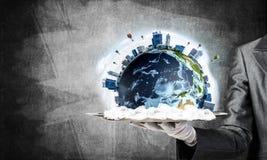 Main de serveuse présentant le globe de la terre sur le plateau Photo libre de droits