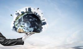 Main de serveuse présentant le globe de la terre sur le plateau Images libres de droits
