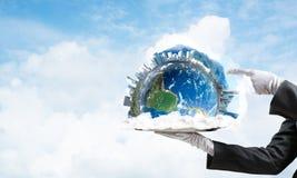 Main de serveuse présentant le globe de la terre sur le plateau Image stock