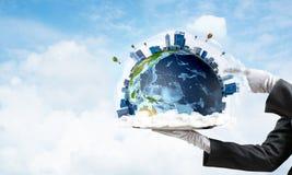 Main de serveuse présentant le globe de la terre sur le plateau Photographie stock libre de droits