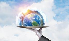 Main de serveuse présentant le globe de la terre sur le plateau Photos libres de droits