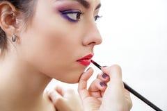 Main de styliste faisant le maquillage professionnel de lèvres avec la brosse Image stock