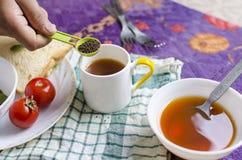 Main de thé noir tenant le thé dans la cuillère de table Photo libre de droits
