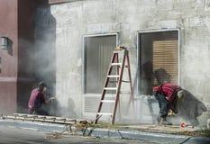Main de travailleur éraflant la vieille peinture sur le mur en béton Vieux décapant Préparation pour peindre un mur photos libres de droits