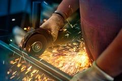 Main de travailleur coupant le métal avec la broyeur images stock