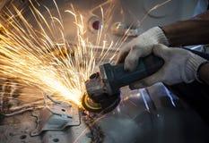 Main de travailleur fonctionnant à côté de l'outil d'industrie coupant l'acier avec la fente fi images stock