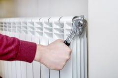 Main de travailleur réparant le radiateur avec la clé Images stock