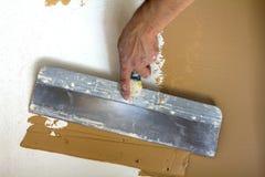 Main de travailleurs de rénovation plâtrant le mur photo stock