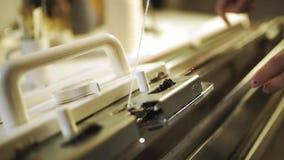 Main de tricoteuse de femme travaillant à la machine de tissage Production de machine à tricoter banque de vidéos