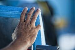 Main de vieil homme sur un bateau de pêche Image libre de droits