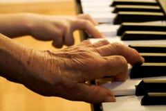 Main de vieux joueur et enfant de piano Photographie stock libre de droits