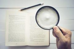 Main de vue supérieure tenant la tasse de café sur le livre dans la table blanche Image libre de droits