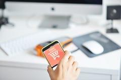 Main de Woman's effectuant une transaction de paiement avec le smartphone sur le terminal de position photographie stock libre de droits