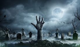 Main de zombi se levant hors d'un cimetière photo stock