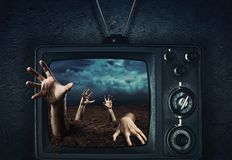 Main de zombi sortant de la TV Photo stock