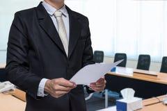 Main debout d'homme d'affaires jugeant de papier sur le fond de lieu de réunion Photos stock