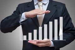 Main debout de posture d'homme d'affaires jugeant des finances de graphique d'isolement sur le fond gris Images stock