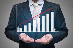 Main debout de posture d'homme d'affaires jugeant des finances de graphique d'isolement sur le fond gris Photos stock