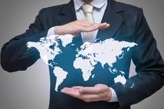 Main debout de posture d'homme d'affaires jugeant la carte du monde d'isolement sur le fond gris Photographie stock libre de droits