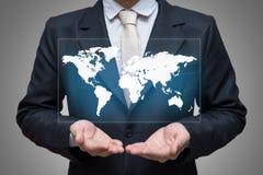 Main debout de posture d'homme d'affaires jugeant la carte du monde d'isolement sur le fond gris Photos stock