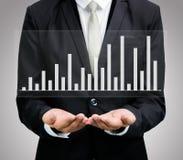 Main debout de posture d'homme d'affaires tenant des finances de graphique Images stock