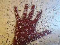 Main derrière la glace avec des baisses Images stock