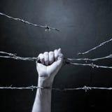 Main derrière le barbelé Images libres de droits