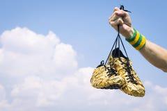 Main des chaussures de Holding Gold Running d'athlète image libre de droits